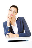 Young business woman sitting and thinking. Royalty Free Stock Images