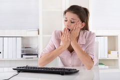 Young business woman sitting tired and yawning in the office. Stock Photos