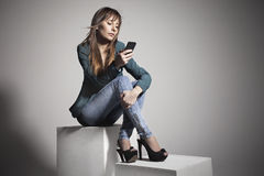 Young business woman sitting and watching a smart phone Royalty Free Stock Photos
