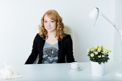 Young business woman sitting at work desk Stock Image