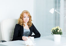 Young business woman sitting at work desk Stock Photos