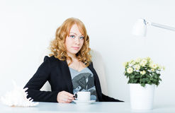 Young business woman sitting at work desk Stock Photography
