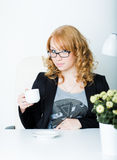 Young business woman sitting at work desk Royalty Free Stock Images