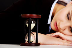 Young business woman sleeping on the desk with hourglass Stock Photo