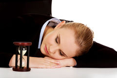 Young business woman sleeping on the desk with hourglass Stock Images