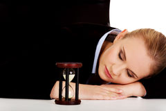 Young business woman sleeping on the desk with hourglass Stock Image