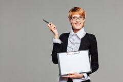Young business woman smiling friendly to the camera while holding a clipboard and a pen Stock Photo