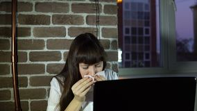 Young business woman sneezing at office with laptop. Young business woman sneezing her face with a paper handkerchief. The brunette sits at the table and works stock video footage