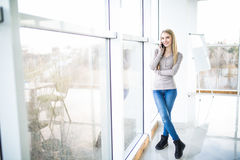 Young business woman speak at phone against panoramic windows Royalty Free Stock Images