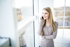 Young business woman speak at phone against panoramic windows Royalty Free Stock Image