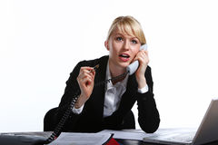 The young business woman speaks by phone. Showing to emotion Royalty Free Stock Image