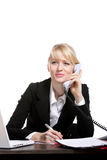 The young business woman speaks by phone. Showing to emotion Royalty Free Stock Photography