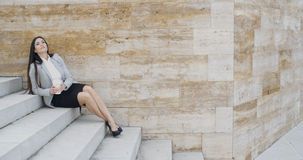 Young business woman on stairs drinking coffee Royalty Free Stock Images