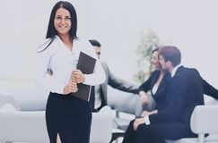 Successful business man standing with his staff in background at Stock Images