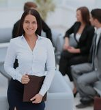 Young business woman standing with her collegues in background a. Successful business woman standing with her staff in background at office Stock Images