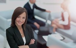 Young business woman standing with her collegues in background a. Successful business women standing with her staff in background at office Royalty Free Stock Photography
