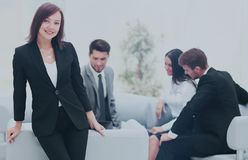 Young business woman standing with her collegues in background a. Successful business woman standing with her staff in background at office Stock Image