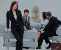 Young business woman standing with her collegues in background a. Successful business women standing with her staff in background at office Royalty Free Stock Photo