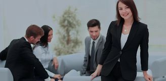 Young business woman standing with her collegues in background a. Successful business women standing with her staff in background at office Stock Photography