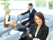 Young business woman standing with her collegues in background a Royalty Free Stock Images