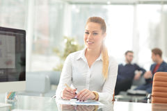 Young business woman standing with her collegues in background a Royalty Free Stock Photo