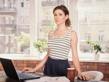 Young business woman standing near her workplace. Portrait of a beautiful business woman standing near her workplace Royalty Free Stock Photography