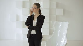 Young business woman stands with a mobile near a white chair in a hi-tech white office stock footage