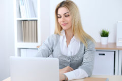 Young business woman or student girl sitting at office workplace with laptop computer. Home business concept Royalty Free Stock Photography