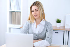 Young business woman or student girl sitting at office workplace with laptop computer. Home business concept Royalty Free Stock Photos