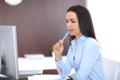 Young business woman or student girl sitting and working with computer in office Royalty Free Stock Photo