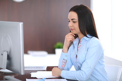 Young business woman or student girl sitting and working with computer in office Stock Photo