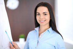 Young business woman or student-girl standing with crossed arms  in office. Blue colored bluse. Education or busines Stock Photography