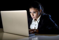 Young business woman or student girl working in darkness on laptop computer late at night concentrated Royalty Free Stock Photo