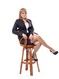 Young business woman in a suit, sitting on bar stool. Young beautiful business woman in a business suit, sitting on a bar stool. White isolated background stock photos