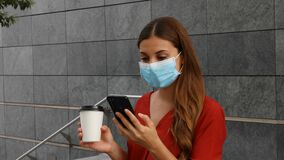 Young business woman with surgical mask holding coffee cup and using her phone while standing outside office building