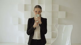 Young business woman takes a bundle of dollars, smells it, smiles and gives back stock video