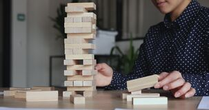 Young businesswoman takes wooden bricks out of tower plays jenga