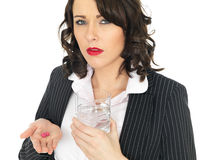 Young Business Woman Taking Medicine Pills. A DLSR royalty free image, of an attractive young business woman, with brown curly hair, holding a glass of water in Stock Images