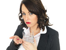 Young Business Woman Taking Medicine Pills. A DSLR royalty free image, of an attractive young business woman, with brown curly hair, holding a glass of water and Stock Photo