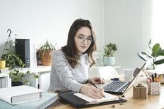 Young business woman taking notes in notebook at office. royalty free stock photo