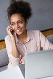 Young business woman talking on mobile phone with laptop Stock Image