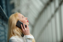 Young business woman talking on mobile phone and looking up Stock Images