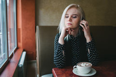 Young business woman talking on the phone and drinking coffee with marshmallows in a cozy cafe. Nooning. Royalty Free Stock Image
