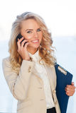 Young business woman talking on phone and holding folder Royalty Free Stock Images