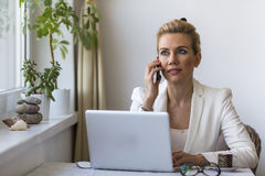 Young business woman talking on the phone while sitting with a laptop. Royalty Free Stock Image
