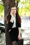 Young business woman talking on the phone under a tree Stock Image