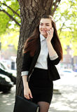 Young business woman talking on the phone under a tree Royalty Free Stock Image