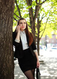 Young business woman talking on the phone under a tree Royalty Free Stock Images