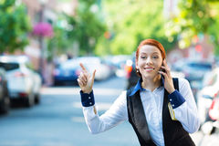 Young business woman talking on smart phone, hails taxi cab Royalty Free Stock Photography