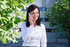 Young business woman talking on smartphone in city park Royalty Free Stock Photography